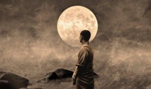 Mand står og ser på måne