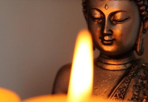 En Buddhastatue foran et lys lærer os at håndtere frygt
