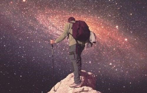 Mand på klippetop ser ud på stjernehimmel