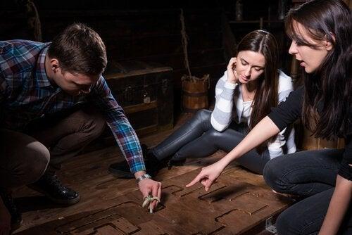 En mand og to kvinder arbejder sammen for at løse et puslespil på gulvet i et escape room