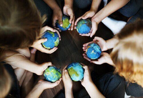 Personer i cirkel holder lille jordklode i hænderne