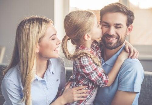 Pige kysser smilende far med mor ved siden af
