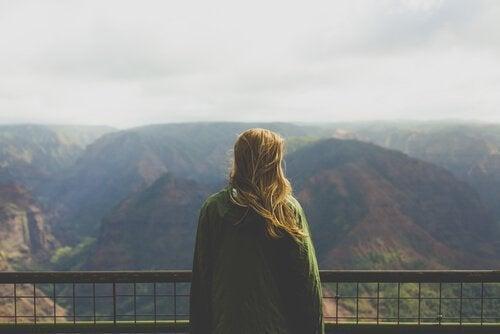 Kvinde beskuer et bjerglandskab
