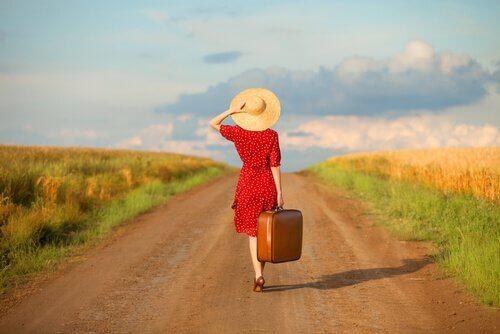 En kvinde med kuffert på en grusvej
