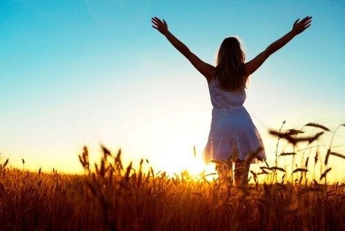 Kvinde med arme over hoved viser glæden ved at komme væk fra det, hvor du ikke kan være dig selv