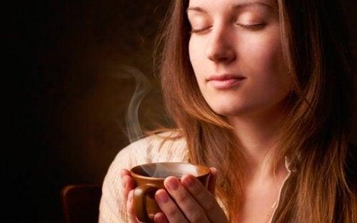 Kvinde med lukkede øjne nyder, at kaffe er stimulerende