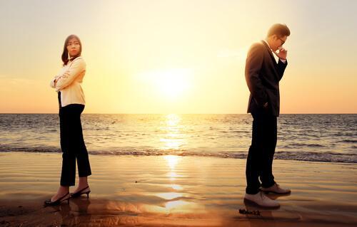 Par på strand står med ryggen mod hinanden efter konflikter i et parforhold