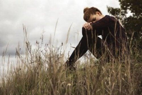 Kvinde sidder alene på eng