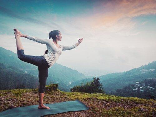 Kvinde dyrker yoga med udsigt over landskab