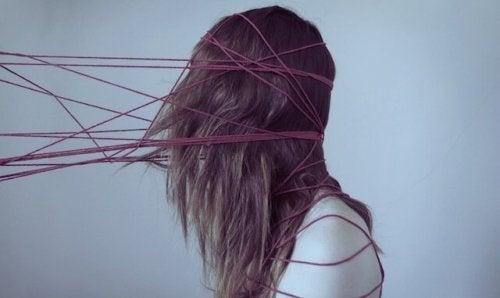 Kvinde er fanget af røde tråde som symbol for kognitive fordomme