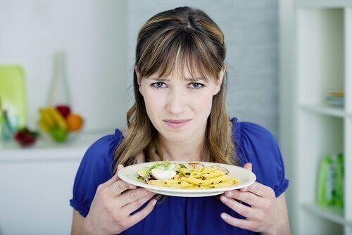 En kvinde, der holder en tallerken med mad og føler afsky