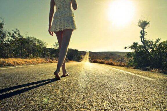 En kvinde går barfodet hen ad en vej