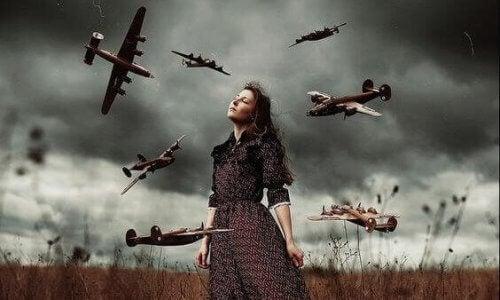 En kvinde står i et felt med en stormfulde himmel bag hende, omgivet af flyvende miniaturefly.