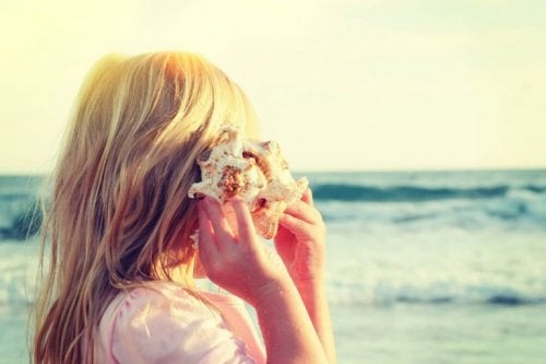 Selektiv opmærksomhed vist via en pige, der lytter til en konkylie på stranden