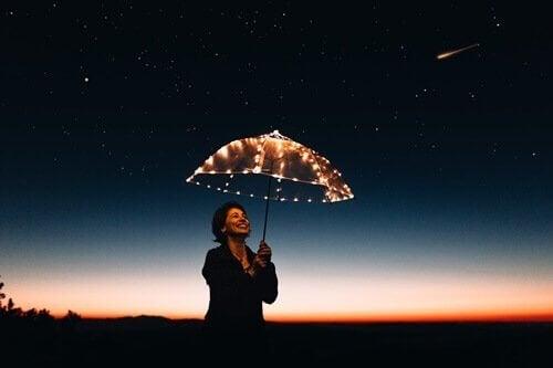 Kvinde under paraply af lyskæder