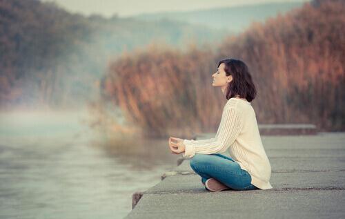 kvinde mediterer i naturen