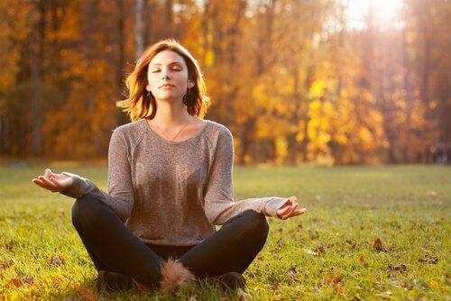Kvinde mediterer i skov
