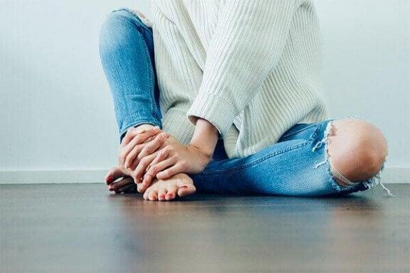 En kvinde sidder på gulvet