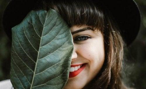 Pige med Duchenne smilet gemmer sig bag blad