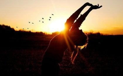 Kvinde med arme over hoved foran solnedgang