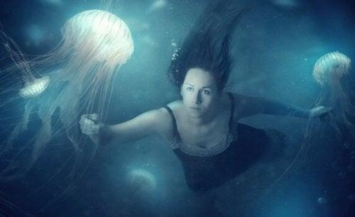 Kvinde svømmer med vandmænd