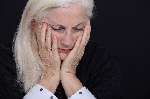 Et close-up af en ældre kvinde med sit ansigt i hænderne