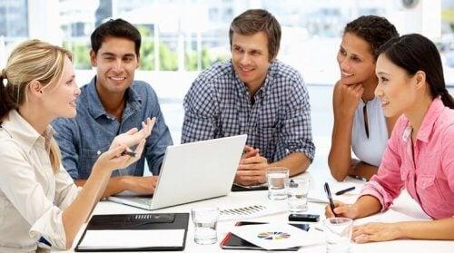 Fem mennesker diskuterer ideer på arbejdspladsen