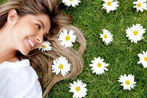 En kvinde ligger ved siden af blomster og smiler