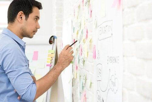 En mand ser på noter på et whiteboard