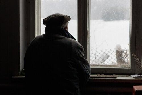 mand der ser ud af vindue