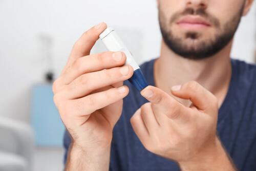 En mand med diabetes kontrollerer sit blodsukker