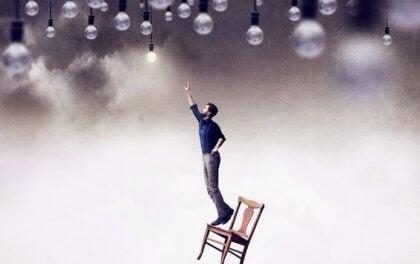Mand på stol rækker ud efter lysende pære i loft