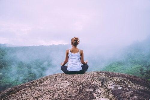 Kvinde mediterer med udsigt over skov