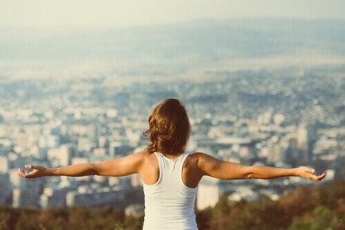 Kvinde står med spredte arme og ser på by
