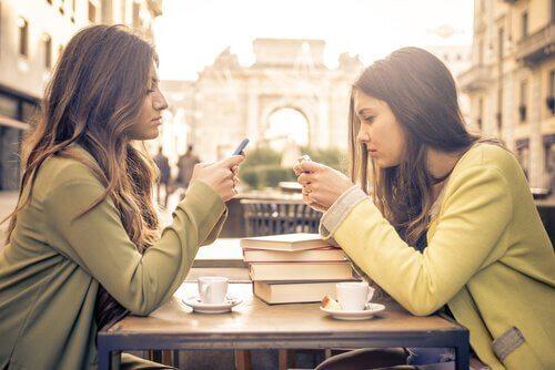 To piger med hver deres telefon