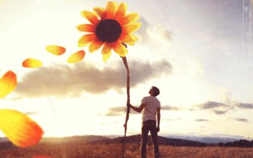 Mand med kæmpe blomst, hvor blade flyver af