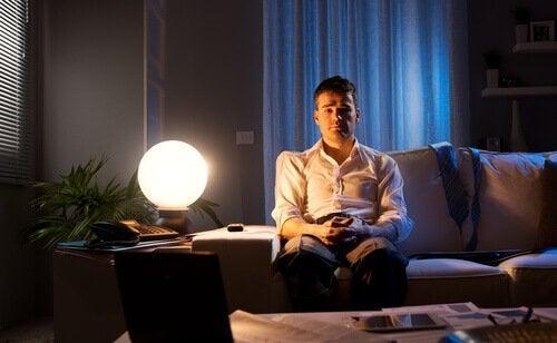 Mand i sofa om natten lider af stressrelateret søvnløshed
