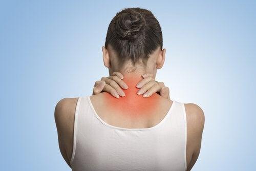 Kvinde tager sig til nakke på grund af smerte