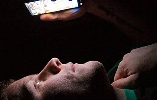 Mand ser på sin mobil i mørket
