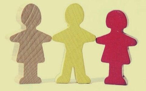 Tre papirdukkefigurer holder hinanden i hænderne