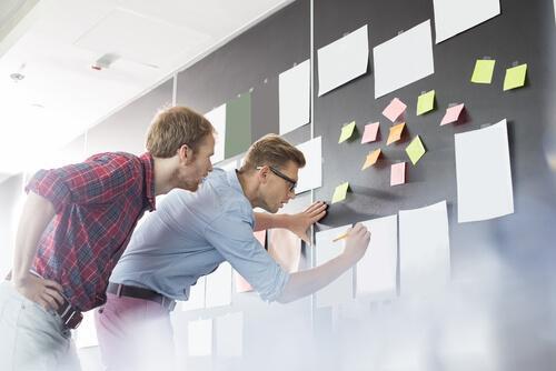 Mand med papir på væg illustrerer, at andres tilstedeværelse påvirker vores indsats