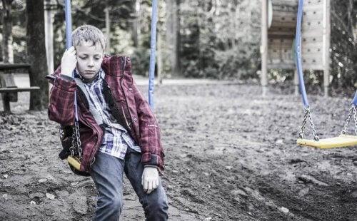 Trist dreng sidder på en gynge og føler, at folk burde vide bedre end til at mobbe