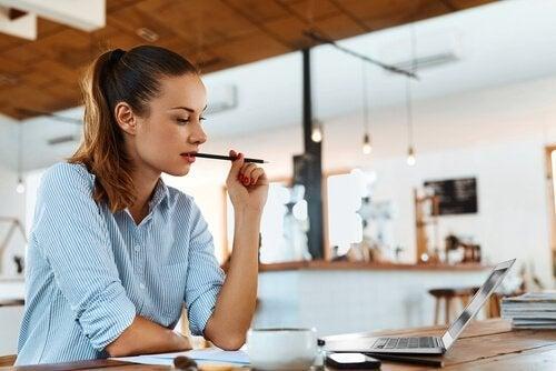 En kvinde kigger eftertænksomt på en bærbar computer