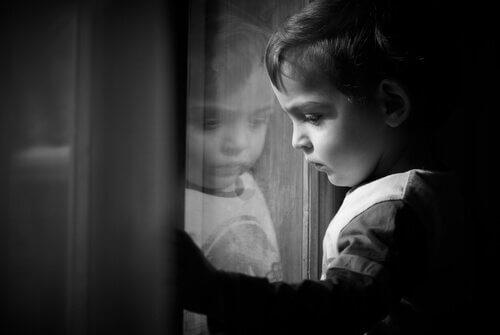Dreng er trist ved vindue