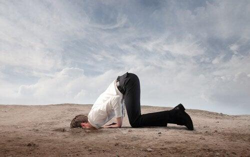 Mand gemmer hoved i sand