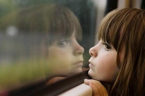 Pige i færd med at dagdrømme og se ud af vindue