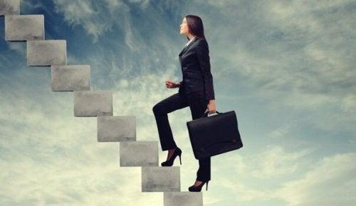 Kvinde med ambition går op ad trapper