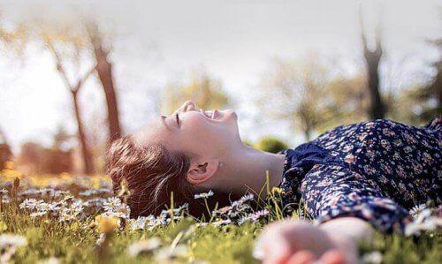 Kvinde på græs forstår, at lykke kommer i små handlinger