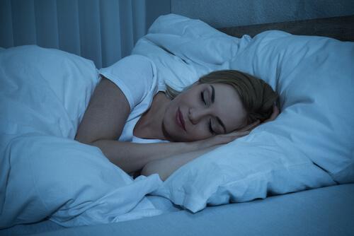kvinde sover i sin seng og nyder en god nats søvn