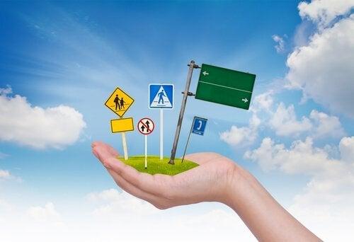 Bedre køreuddannelse illustreres af hånd med vejskilte